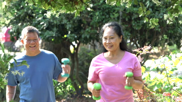 A senior Asian couple exercising In the park, walking with hand weights. The woman, in her 60s, is in front. She turns to look at her husband, in his 70s.